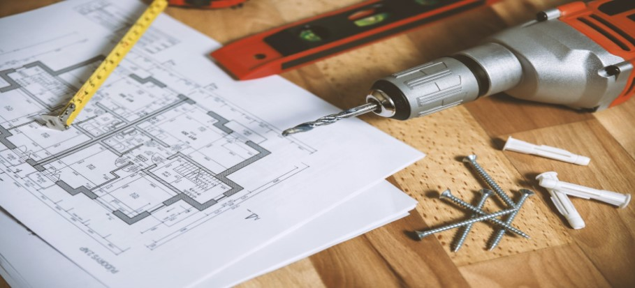 construction plans and a drill