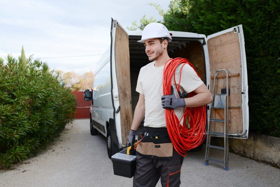happy electrician with a bunch of cables over his shoulder