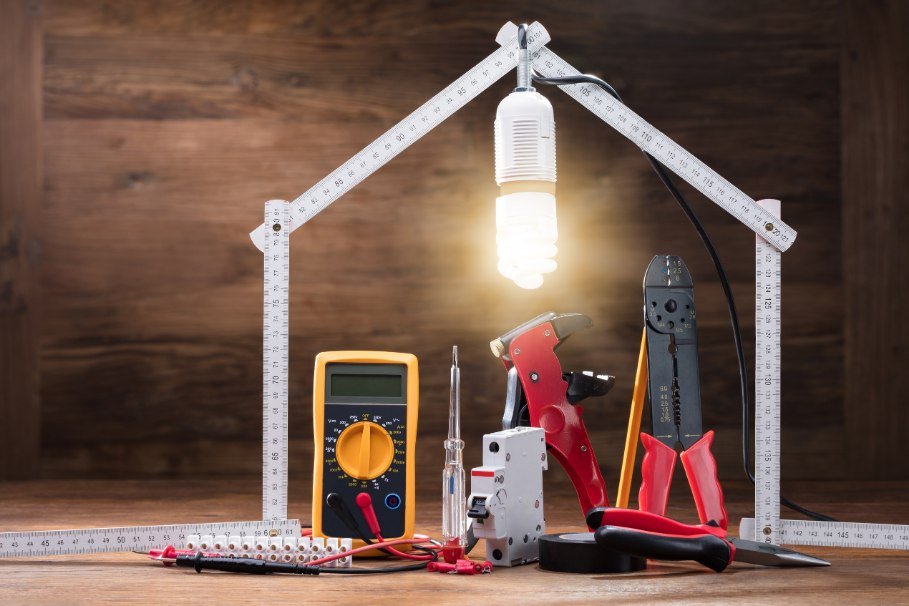 a working light bulb over electrician tools